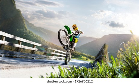 Professional enduro bike rider makong wheely. Turn on sand terrain.