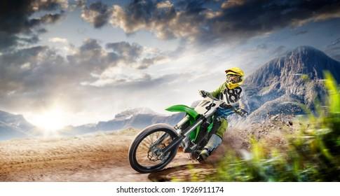 Professional enduro bike rider on action. Turn on sand terrain.
