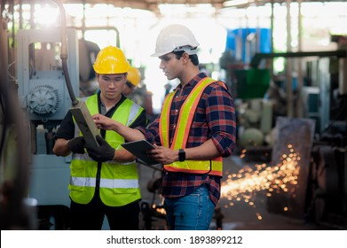 Professional engineer male and technician Machine operator control is training and checking operating in factory and the back has sparks from metal cutting. Due to the maintenance of machinery
