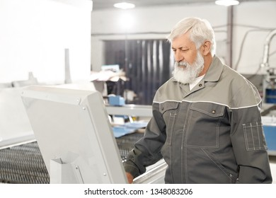 Professional engineer wearing in protective clothes, working in factory with metalwork and laser plasma cutting. Elderly bearded man operating computerized machine.