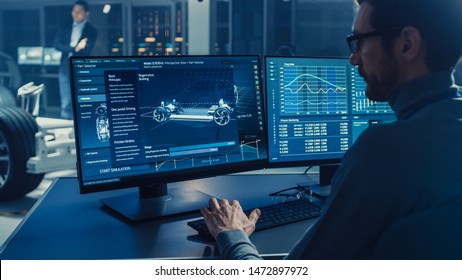 Professional Engineer Works on a Computer with a 3D CAD Software and Tests the Electric Car Chassis Prototype with Wheels, Batteries and Engine Standing in a High Tech Development Laboratory.