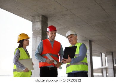 Professional engineers in safety equipment at construction site