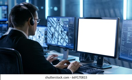 Professional IT Engineers Working in System Control Center Full of Monitors and Servers. Possibly Government Agency Conducts Investigation. He Works With White Screen Isolated. Good for Template.