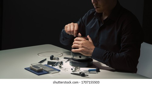 Professional engraver tools for jewelleries manufacturing on white desk. Craftsman, engraver, goldsmith workplace. Mans hand closeup. Low light dramatic photo Jewelry craftsmanship, engraving concept.