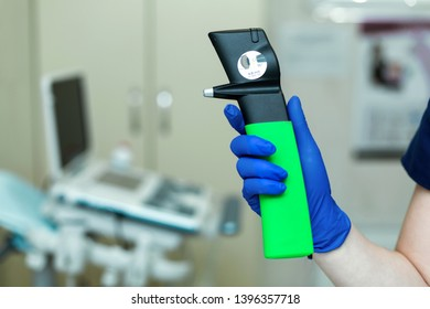 Professional equipment ophthalmologist tonometer.Doctor vet holds in his hand with a glove veterinary tonometer.Blurred background.