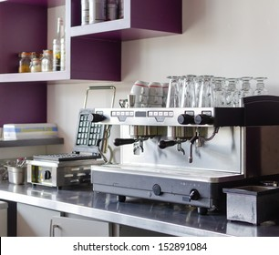 A professional espresso coffee maker, ideal for cafes and bars. Stored over it are late glasses and a waffle maker next to it