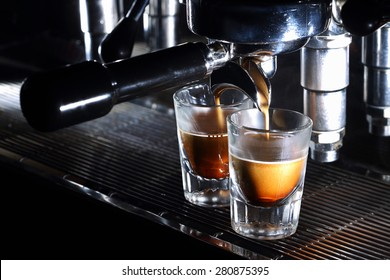 Professional espresso machine brewing a coffee. Coffee pouring into shot glasses. Toned image