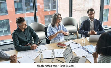 Professional executive businesspeople discuss corporation project planning sit at meeting table in boardroom. Company managers brainstorm financial plan working together with document papers in office - Shutterstock ID 2036186306