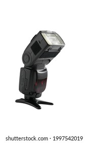 A professional, expensive external remote photography digital travel flash standing on a table tripod, cut out on white background with copyspace.