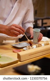 Professional and experienced sushi chef carefully add final touch with confident and dedication to his perfect sushi. Precision and Finesse at its best practice to achieve top performance in business.