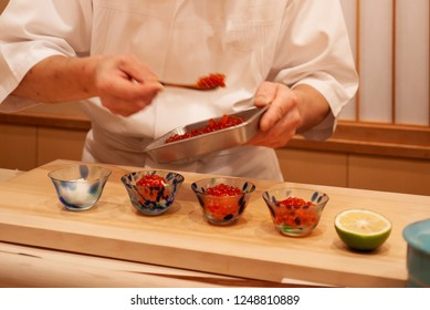 Professional and experienced sushi chef carefully spoon delicious and top quality ikura or Salmon roe to make sushi. Precision and Finesse at its best practice to achieve top performance in business
