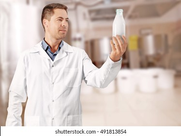 Professional expert with glass bottle of milk on blurred dairy equipment background. Dairy product concept.