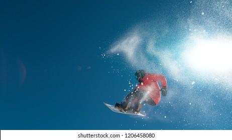 Professional extreme snowboarder spins through the air while holding his board. Cinematic shot of pro male rider doing a cool trick while snowboarding in a beautiful ski resort in sunny Slovenia.