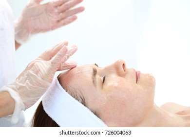Professional face massage. Woman in beauty parlor during facial massage.