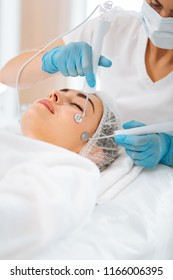 Professional facial therapy. Nice beautiful woman lying with her eyes close while having a microcurrent therapy session