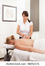 Professional female acupuncturist working with a female patient in a clinic