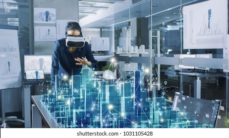 Professional Female Architect Wearing  Augmented Reality Headset Work with 3D City Model. High Tech Office Use Virtual Reality Modeling Software Application.