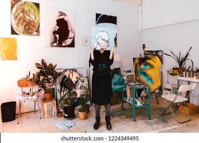 professional female artist painter working in her studio atelier