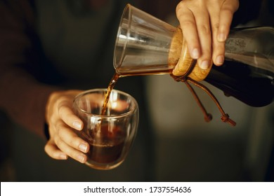 Professional female barista in black uniform making drip coffee. Person pouring fresh aromatic coffee from glass flask in cup, hands close up. Alternative coffee brewing.