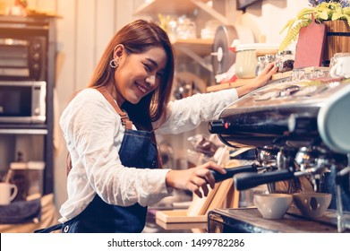 Professional female barista hand making cup of coffee with coffee maker machine in restaurant pub or coffee shop. People and lifestyles. Business food and drink concept.  Happy shop owner entrepreneur