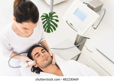 Professional female beautician making facial peeling