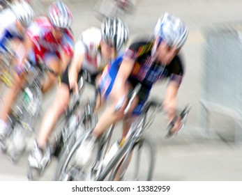 Professional female bicycle racers rounding a turn, intentionally blurred