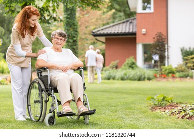 A professional female caregiver with her impaired geriatric patient on a wheelchair outside in the garden.