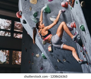 Professional female climber hanging on the bouldering wall, practice climbing indoors.