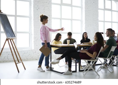 Professional female coach speaking during training seminar explaining new information to increase students knowledge, skilled leader of working crew discussing ideas for new startup project in office