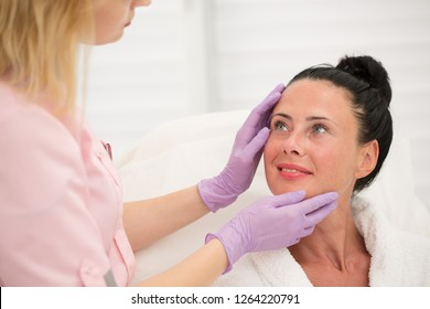 Professional female cosmetologist examining face skin of beautiful woman in beauty parlor. Pretty patient in white robe looking at serious doctor in uniform and protective gloves.