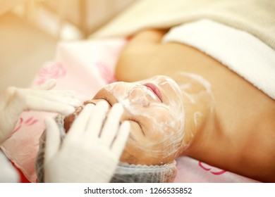 Professional female cosmetologist make up remover for asian famel model. Beautiful woman having a beauty procedure in Cosmetology clinic. Beauty, skeen, care concept image.