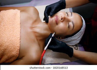 A professional female cosmetologist perform a hydrafacial procedure in a cosmetology clinic. The doctor cleans the pores of the face with a vacuum. Rejuvenation and hydration in the spa