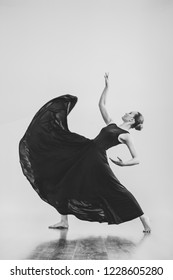 Professional female dancer in black dress dancing flamenco in studio isolated background. Beautiful young woman girl posing indoors natural light black and white copy space choreography card arts