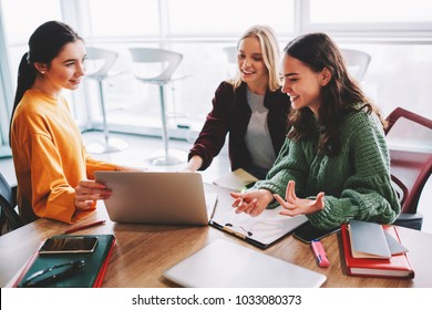 Professional female designer showing business plan to successful colleagues on netbook.Cheerful students watching tutorial on laptop.Positive employees discussing work's schedule sitting at computer