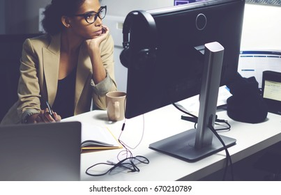 Professional female editor sitting in studio while choosing video for prime time watching media materials on modern computer connected to free wireless internet in newsroom during working day
