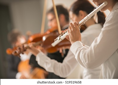Professional female flustist playing her instrument on stage with classical music symphony orchestra, unrecognizable person