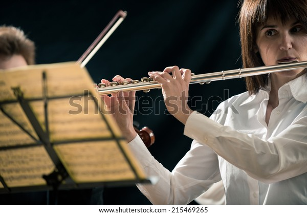 Professional female flutist performing on stage with sheet music.
