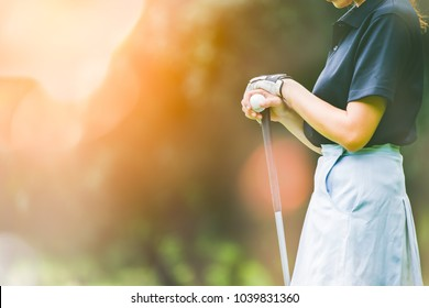 Professional female golfer holding golf club on field and looking away.Asian woman play golf