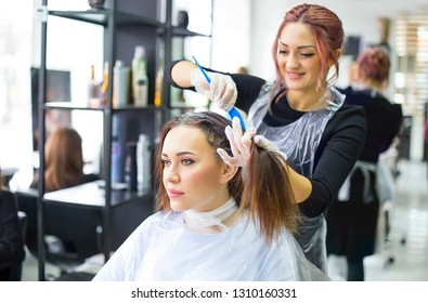 Professional female hairdresser applying color to female customer at design hair salon, woman having her hair dyed. Hair dye colouring in process