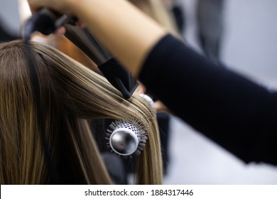 Professional female hairdresser drying woman's hair styling using blow dryer at the hairdressing saloon