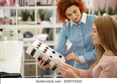 Professional female hairdresser working at her salon helping her female client choosing hair dye color from the chart copyspace profession occupation job career beauty industry service communication.