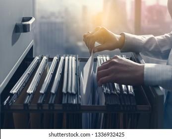 Professioneller Büroangestellter, der Dateien und Papiere im Aktenschrank sucht