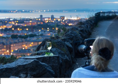 Professional female photographer with digital SLR during photography workshop. Image with focus on wine glass