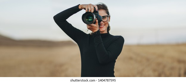 Professional female photographer with dslr camera photographing outdoors. Young woman with camera taking pictures.