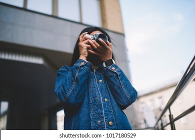 Professional female photographer making photo on vintage camera while spending time outdoors.Young hipster girl fond of photography enjoying hobby of taking pictures of city streets and urban settings