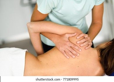 Professional female physiotherapist giving shoulder massage to brunette woman in hospital. Medical check at the shoulder in a physiotherapy center.
