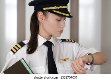 Professional female pilot checking the time on her watch