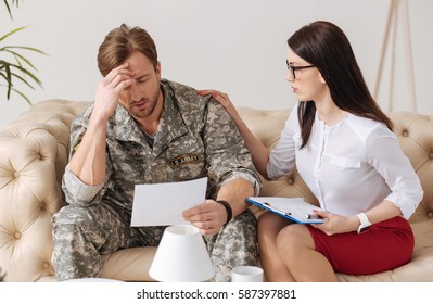Professional female psychologist sitting near her patient