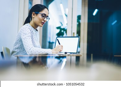 Professional female secretary staying in office overtime for doing report at desktop, pensive young woman preparing for college examinations late in evening making notes and analyzing information