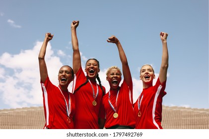 Professional female soccer players celebrating a victory on a sports arena. Group of woman football players screaming and punch air after winning the championship on sports field.